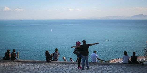 Couples observe a panoramic view of the Gulf of Tunis from the touristic village of Sidi Bou Said, some...