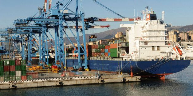 'Large modern container boat arriving at the dock, several elevators ready for unloading, Genoa,