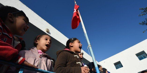 Tunisian schoolchildren sing their national anthem in a primary school in the Tunis suburb of Ariana...