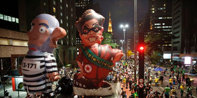 Demonstrators march alongside large, inflatable dolls depicting Brazil's former President Luiz Inacio...
