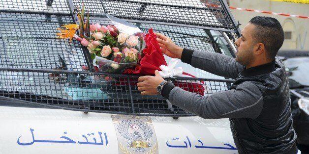 Le 25 novembre 2015, un homme place des fleurs sur un véhicule de police, à proximité des lieux de l'attentat...