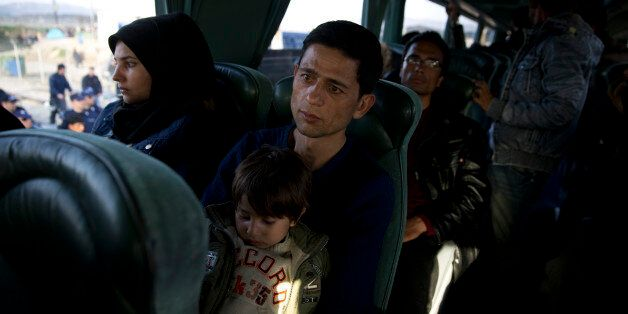 An Afghan family sit inside a bus as they leave with others the northern Greek border station of Idomeni,...