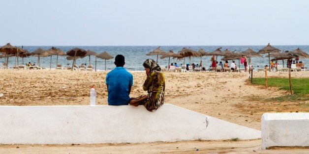 In this photo taken on Aug. 9, 2015, a Tunisian couple sit on the sea wall watching the beach in Hammamet,...