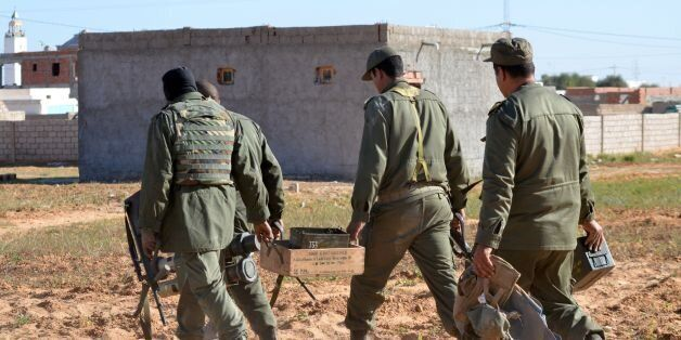 Tunisian special forces carry boxes of ammunition left behind by jihadists in the southern town of Ben...