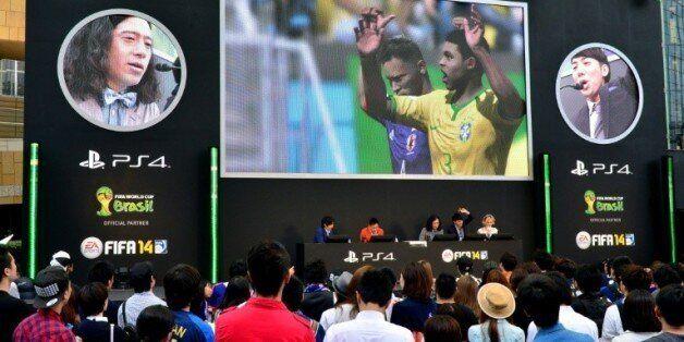 Des fans assistent, sur un écran géant, à un match de foot sur PlayStation à Tokyo, le 4 juin