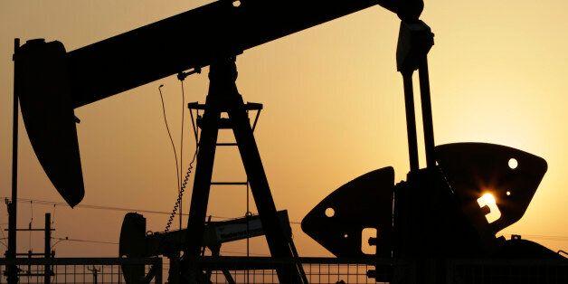 oil pumps work in the desert oil fields of Sakhir,