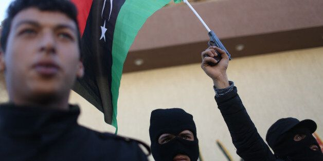 Libyan security forces stand in front of the security headquarters, one showing his weapon with a Libyan...