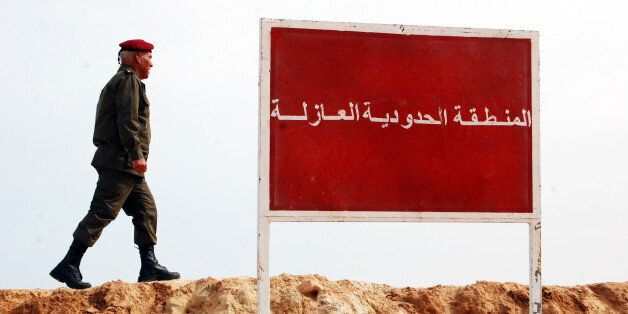 A Tunisian soldier walks on a sandbank near a board