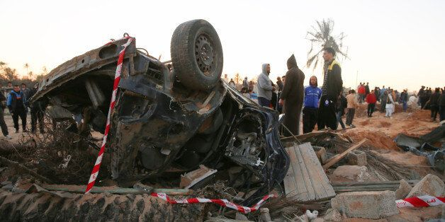In this Friday, Feb. 19, 2016 photo, people gather by the wreckage of a car, after an air strike on a...