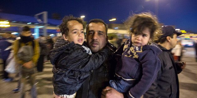 A man carrying two children arrives at the port of Piraeus, near Athens, on Saturday, Feb. 20, 2016....