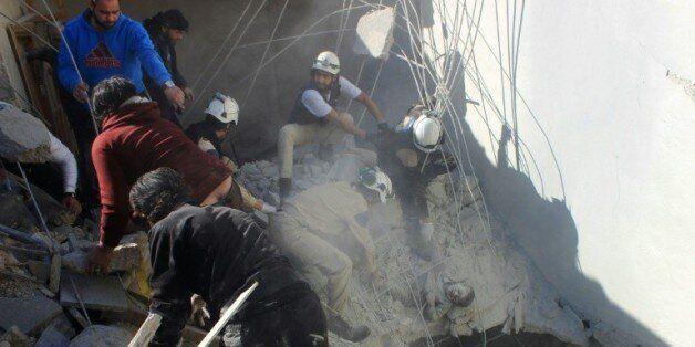Des secouristes extraient un garçon des gravats après un raid aérien à Alep le 16 février