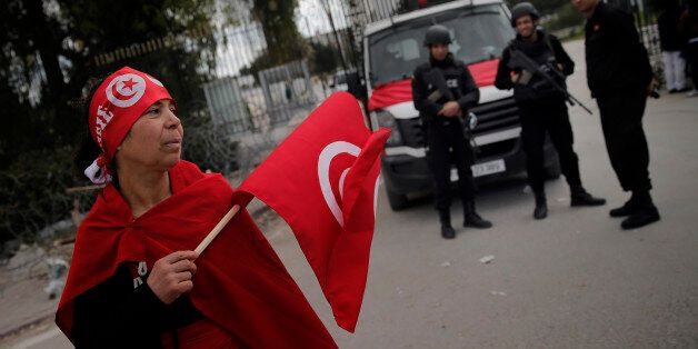A woman holds a Tunisian flag as policemen stand guard at the National Bardo Museum two days after gunmen...