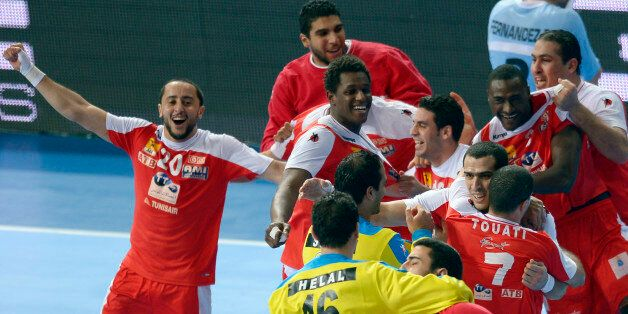 Tunisia's players celebrate their victory over Argentina during a preliminary round Group A Men's World...
