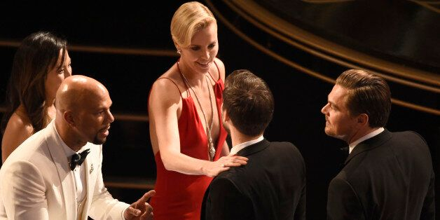 Common, from left, Charlize Theron, Tobey Maguire, and Leonardo DiCaprio are seen in the audience at...