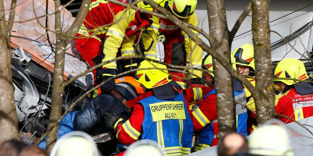 Rescue workers salvage a body at the site where two trains collided head-on near Bad Aibling, southern...