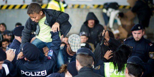 Des policiers autrichiens aident des migrants à traverser la frontière
