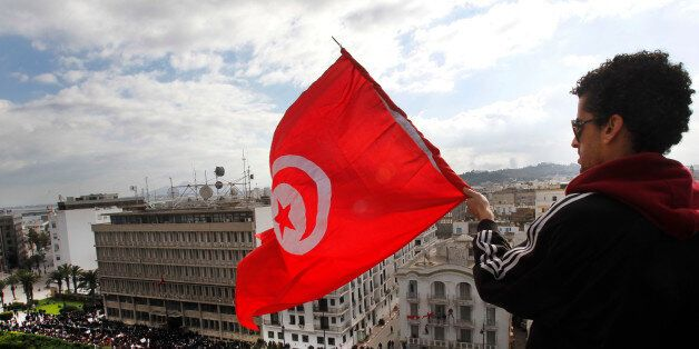 A protester waves the Tunisian flag as he watches a demonstration against President Zine El Abidine Ben...