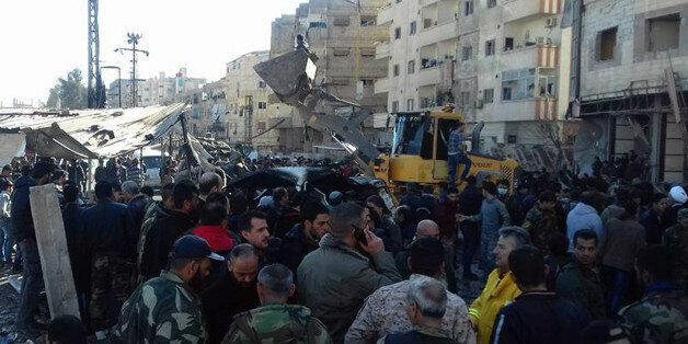In this photo released by the Syrian official news agency SANA, Syrians gather where three bombs exploded...
