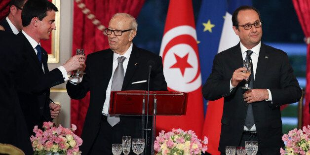 Tunisian President, Beji Caid Essebsi, center, shares a toast with French Prime Minister, Manuel Valls,...