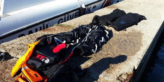 Dead bodies of migrants lie on the ground in Seferihisar port near Izmir, Turkey, Tuesday, Feb. 2, 2016....