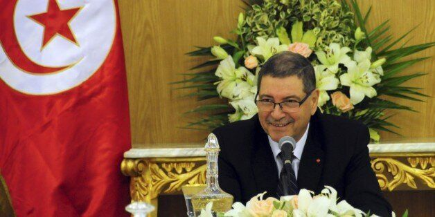 Tunisia's Prime Minister Habib Essid shares a smile with ministers prior to preside over an extraordinary...