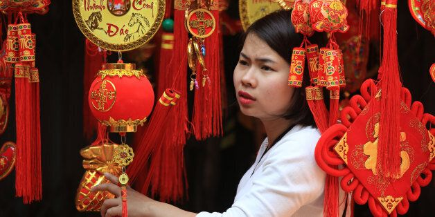 A woman looks at Lunar New Year decorations in the old quarter of Hanoi, Vietnam on Saturday, Feb. 6,...