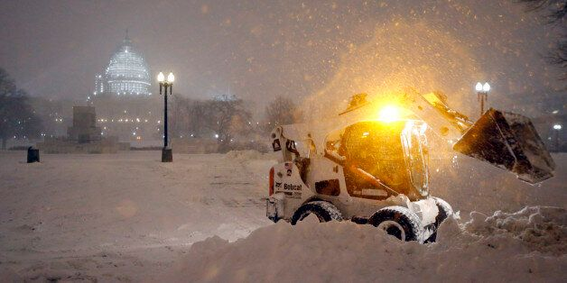A bobcat piles up snow in front of the U.S. Capitol, as the snow continues to fall, Friday, Jan. 22,...