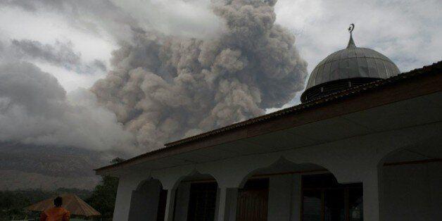 Un Indonésien se tient près d'une mosquée dans le village de Tiga Serangkai dans le nord de Sumatra,...