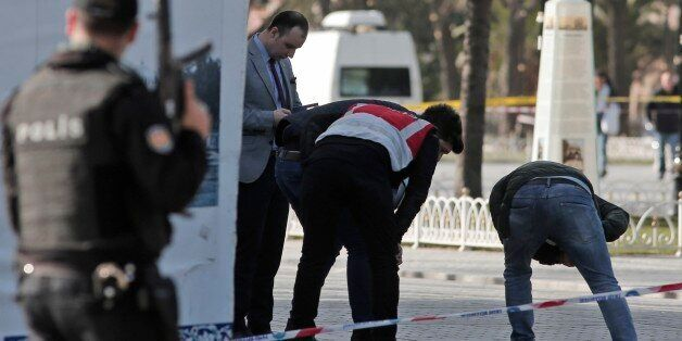 Police search the area at the historic Sultanahmet district after an explosion in Istanbul, Tuesday,...