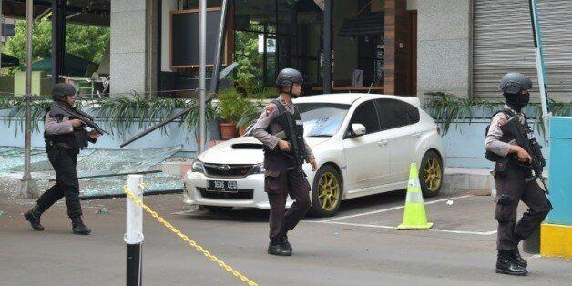 Des policiers indonésiens devant le café Starbucks détruit lors des attentats à Jakarta, le 14 janvier