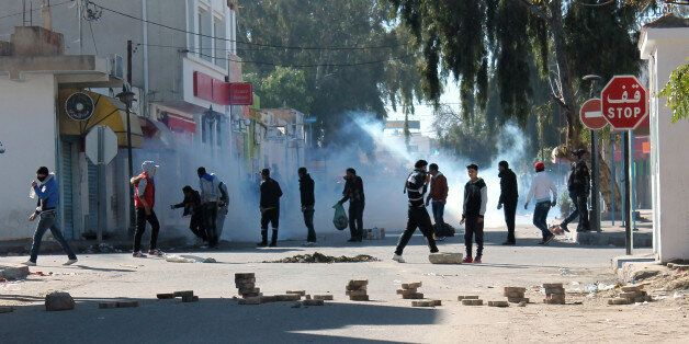 Tunisian protesters take to the streets in the southern town of Kasserine , Tunisia, and clash with riot...