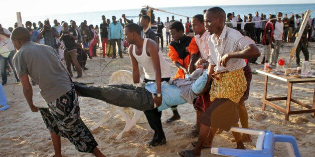 Relatives carry away a dead body from the beach following an overnight attack on a beachfront restaurant...