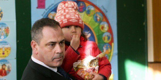 Le Britannique Robert Lawrie tient dans ses bras une petite réfugiée afghane de quatre ans, Bahar Ahmadi,...