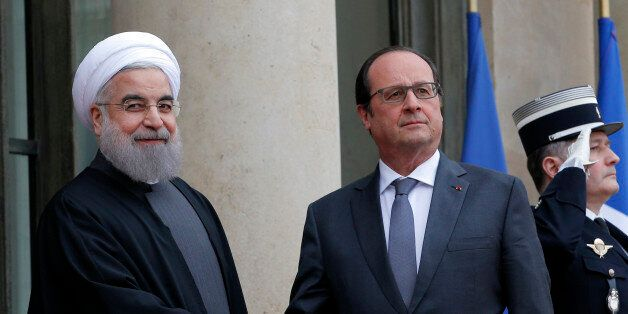 French president Francois Hollande, right, welcomes Iranian President Hassan Rouhani before a meeting...