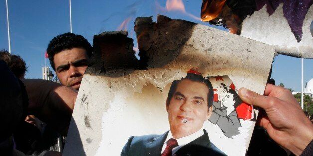 FILE - In this Monday, Jan. 24, 2011 picture, protestors burn a photo of former President Zine El Abidine...