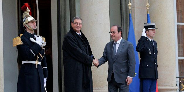 French President Francois Hollande, right, greets Tunisian Prime Minister Habib Essid before a meeting...