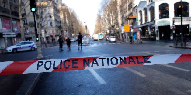 Police officers cordon off the area of a fatal shooting which took place at a police station in Paris,...