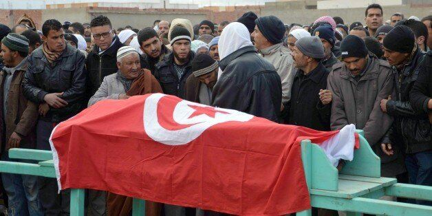 Mourners carry the coffin wrapped by the Tunisian flag of one of the four national guards killed in an...