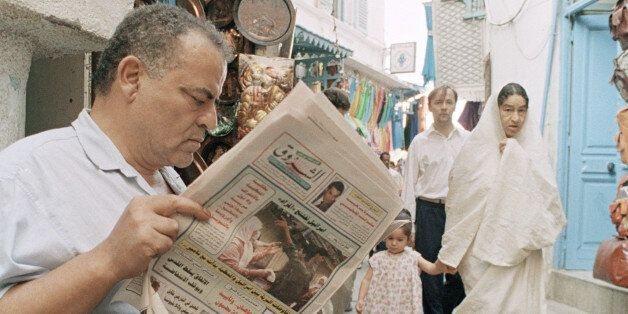 An unidentified Tunisian reads news of the ongoing meetings of the Fatah faction of the Palestinian Liberation...