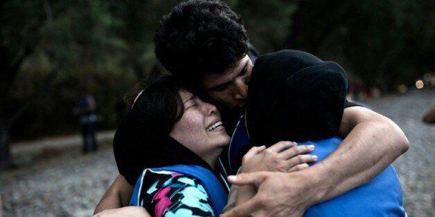 Des gens se réconfortent mutuellement à leur arrivée sur l'île grecque de Lesbos, après une traversée...