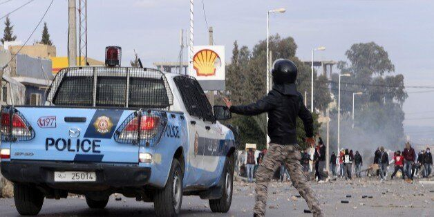 Protesters face police forces in the city of Ennour, near Kasserine, Tunisia, Wednesday, Jan. 20, 2016....