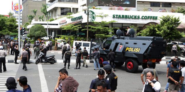 Police officers stand guard outside a Starbucks cafe near where an explosion went off in Jakarta, Indonesia...