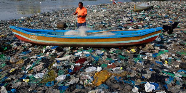 A fisherman prepares his net on the shores of the Arabian Sea, littered with plastic bags, in Mumbai,...