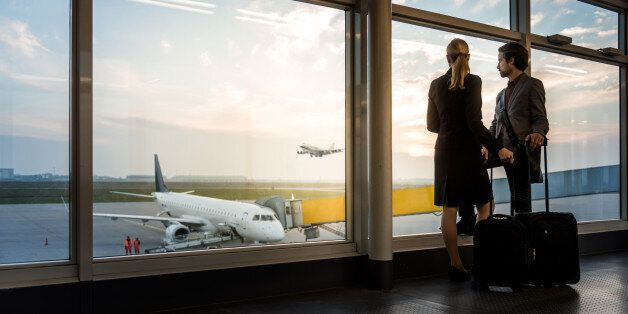 two business travellers standing at airport window and overlooking the