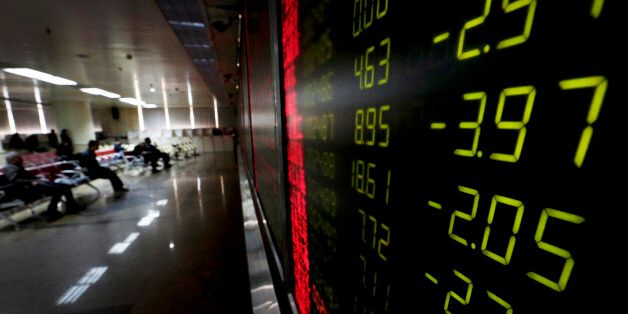 An electronic board display stock prices at a brokerage house in Beijing, Thursday, Jan. 14, 2016. Asian...