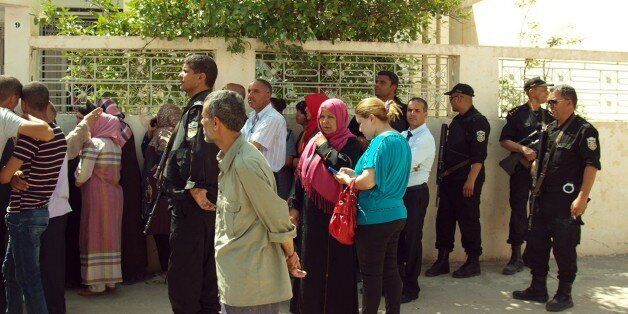 Bystanders gather in front of Tunisian Interior Minister Lotfi Ben Jeddou's residence in Kasserine, southern...