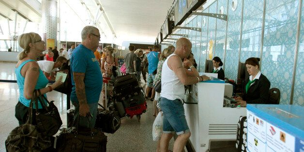 Tourists line up at a boarding desk as the leave Sousse, Tunisia, after the attack, Saturday June 27,...