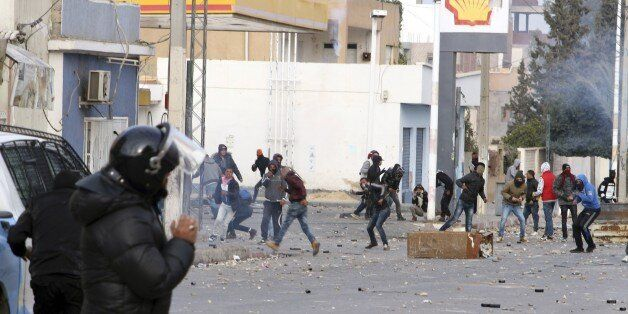 Protesters throw items to police forces in the city of Ennour, near Kasserine, Tunisia, Wednesday, Jan....