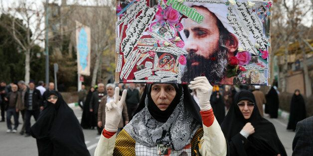 An Iranian worshipper holds up a poster showing Sheikh Nimr al-Nimr, a prominent opposition Saudi Shiite...