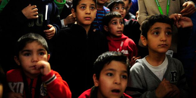 SARSTEDT, GERMANY - DECEMBER 24: Children from Syria and Afghanistan look at a volunteer dressed as Santa...